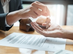 Real Estate agent Handing Over Keys to investor at a table, over the signed contract