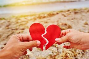 A close up of an investor broken heart, held in their hands, on a beach at sunset