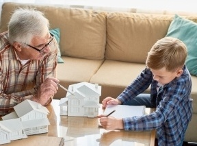 Grandpa teaches his grandson about real estate while working at a coffee table near a tan couch & wearing plaid button ups - BLOG