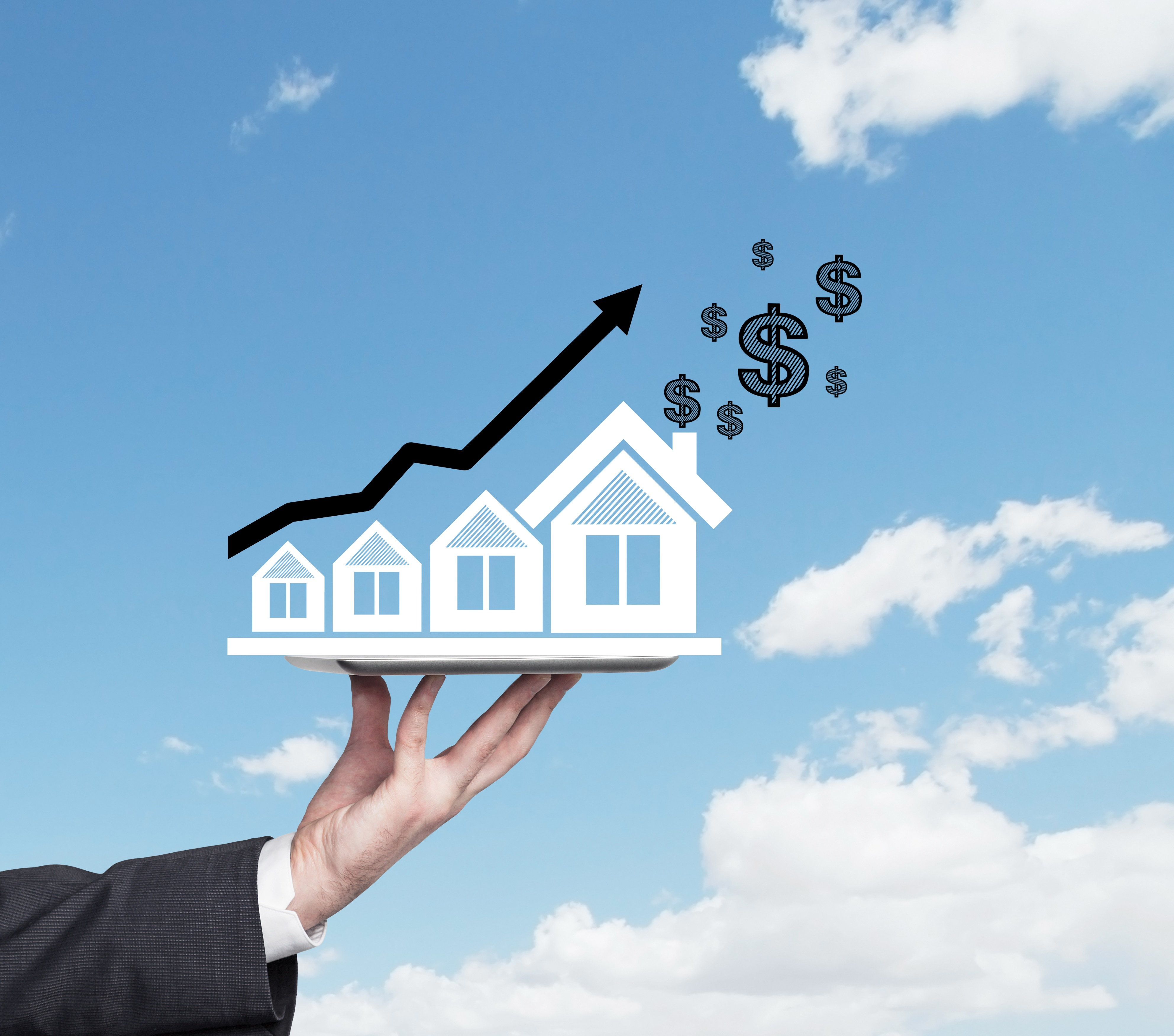 Business man's Hand holding a house against a blue sky, with bar graph above, showing growth and $$$ in the distance