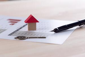 Small wooden house, key, pen, and mortgage note details sitting on a desk, waiting to be considered by investors
