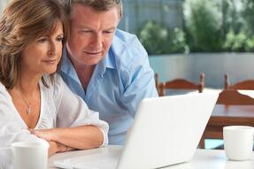 A Confused Couple looks at a laptop, confused about Spousal Consent