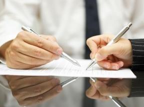 Man's hand showing a woman's hand sign IRA divorce paperwork