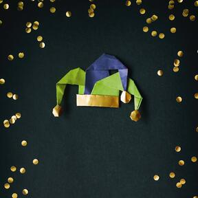 black background with gold circular confetti, a green, purple and gold jester hat sits in the middle of the frame