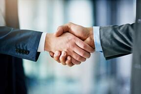 2 businessmen in suits shaking hands, agreeing to partner on a real estate IRA deal