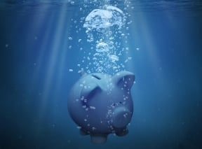 A piggy bank is sinking into deep water, representing an IRA asset that is underwater and has no value