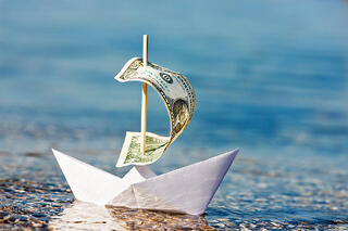 paper boat with a dollar as a sail floating away due to prohibited transactions