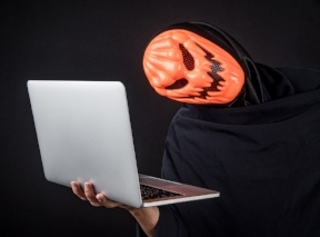A creepy man in a pumpkin halloween mask stands holding a computer, scamming your self-directed IRA - BLOG